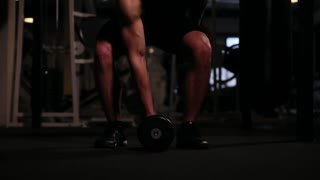 A professional athlete performs one weight in the gym