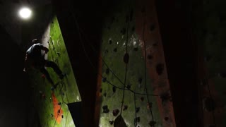 a professional climber descends on a safety rope of the last victory and competitions in rock climbing. Descent on the insurance. Male climber
