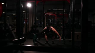 A sports athlete in the gym raises the bar with a weight above his head from the sitting position