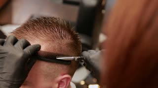 A woman Barber in the barbershop shop to put customer's man in a chair and begins to conduct his haircut
