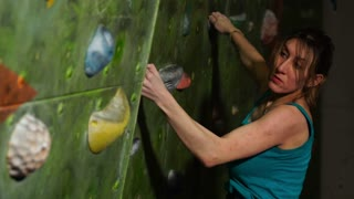A woman climber is trained to overcome obstacles on the wall for rock climbers. Professional rescuer