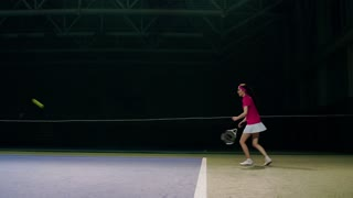 A woman in a pink t-shirt and a white skirt plays off the balls during a tennis match. The tennis player learns to play. Training tennis competition on a closed court in slow motion.