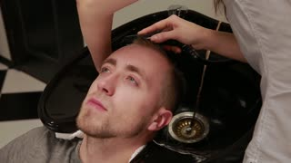 A woman washes her hair in the Barber shop bearded man with shampoo and conditioner. Wash off the shampoo water