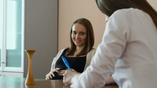 A young beautiful pregnant woman in a black T-shirt is talking to a young female doctor in a white coat in her office in the hospital. Consultation of doctor and patient. The doctor prescribes the
