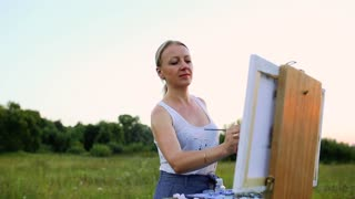 A young woman with long hair that develops in the wind paints a picture on canvas, which stands on the easel. The lady is in an open air, she draws from life