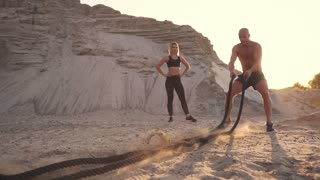 Athletic man on exercise around the sand hills at sunset hits the rope on the ground and raised the dust.