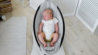 Baby sleeps in a rocking chair for children high-tech design in white bedroom