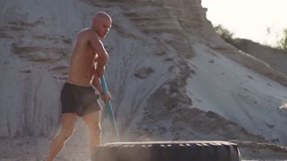 Bald man strongman hits a hammer on a huge wheel in the sandy mountains in slow motion. strength and endurance training for wrestlers.