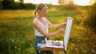 beautiful blonde woman artist with a brush in her hand draws on canvas in the nature
