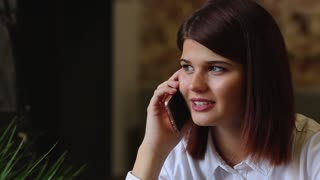 Beautiful business woman talking on the phone smiling and talking about her trip on vacation. Close-up