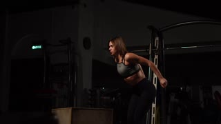 Beautiful female fitness athlete performs box jumps in a dark gym wearing black sports top and short tights with face hidden