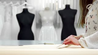 Beautiful girl fashion designer draws on the paper templates for cutting out fabric on the mannequins dressed in wedding dresses. Manufacturer of wedding dresses.