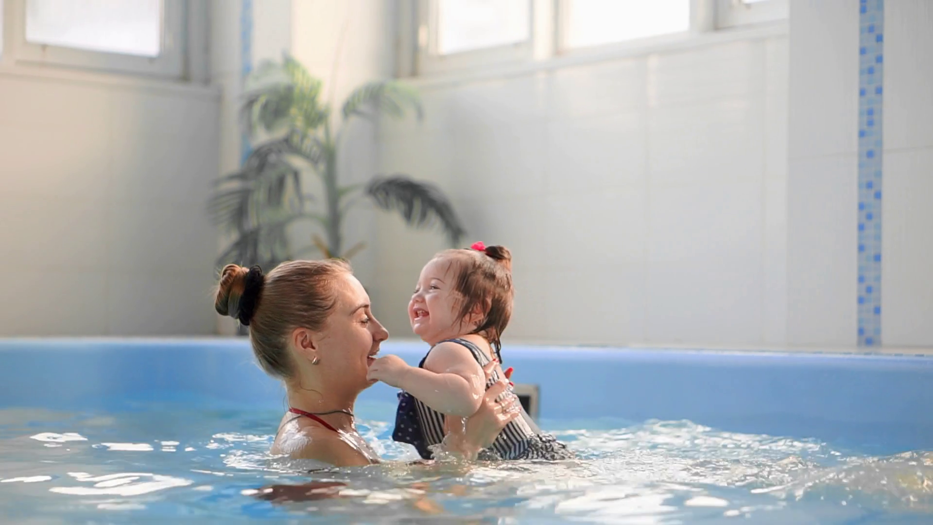Beautiful mother teaching cute baby girl how to swim in a swimming pool. Child having fun in water with mom. Stock Video Footage - Storyblocks