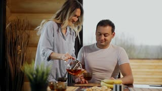 Beautiful woman in pajamas pours her husband tea, hugging him in the kitchen and drink tea. Lovers