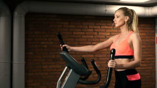 Beautiful woman portrait at the gym cycling