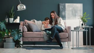 Beautiful young mother sitting on the sofa in your house the living room reads son a story in the ear and learn to read little boy