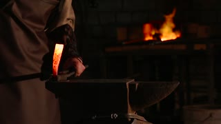 Blacksmith brings dripping hot metal from furnace and creates a shower of sparks as he beats a piece of white hot metal with a hammer on an anvil. Close up recorded.