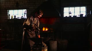 Blacksmith brings dripping hot metal from furnace and creates a shower of sparks as he beats a piece of white hot metal with a hammer on an anvil.
