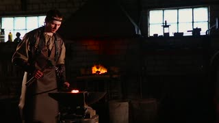 Blacksmith working in the forge hot metal
