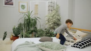 Boy 5-7 years old in blue jeans and a gray sweater European appearance happily jumping on the bed in the parents ' bedroom with a toy bear and pillow