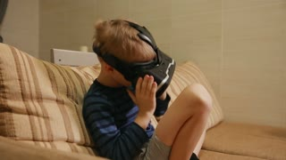 Boy 6-7 years playing at home with the help of virtual reality goggles video games. Close-up