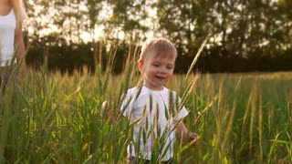 Boy in white shirt walking in a field directly into the camera and smiling in a field of spikes