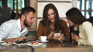 Cheerful teen hipster guy looking at camera while showing her girlfriend video on smartphone, romantic couple in love spending time together on cafe terrace viewing funny photos on mobile phone