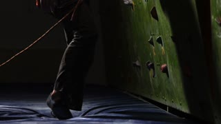 Close-up a male climber begins climbing the wall of the climbing wall with insurance in rocks