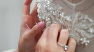 Close-up fashion designer for brides in his Studio pins needles lace wedding dress. Seamstress creates an exclusive wedding dress. Secure with pins and needles outline. Small private business. Sew