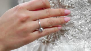 Close-up fashion designer for brides in his Studio pins needles lace wedding dress. Seamstress creates an exclusive wedding dress. Secure with pins and needles outline. Small private business