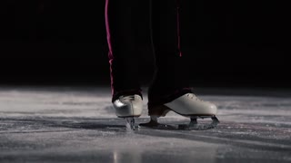 Close-up, legs in ice skates go to the ice and move in the frame. The camera moves dynamically behind the skates. Professional figure skating