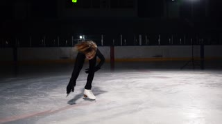 Close-up of a girl skater on ice carries out a rotation around her axis while standing on ice skates on one leg. Camera moves in orbit around the figure skater in slow motion