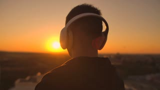 Close-up of a man in headphones looking at the city from the height of a skyscraper at sunset. Relax while listening to music. Enjoy a beautiful view of the city at sunset from roof with headphones