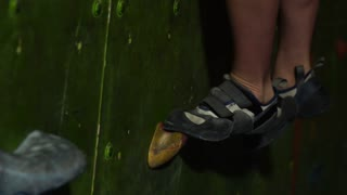 close-up of feet shod in shoes for rock climbing overcome obstacles on the climbing wall