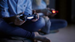 Close-up of hands using a wireless joystick for games on the console at night. The light from the TV. Two people
