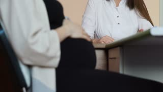 Close-up of the belly of a pregnant woman at the doctor's desk and the focus gradually turns to the doctor in the background. Dialogue of the future mother with a doctor in the office
