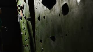 Close-up of the hand of a woman climber who climbs on the climbing wall along the wall tripping for competitions without insurance. Slow motion. Blonde