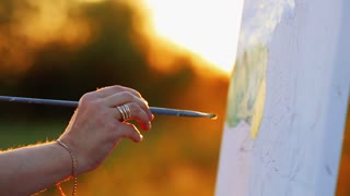 Close up view of female artist painting picture outdoors