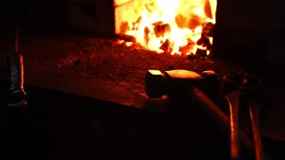 Closeup of a blacksmith fanning the flames of the furnace, using the tools prevents embers, sparks flying to the side in slow motion. Close-up of blacksmith's hand.