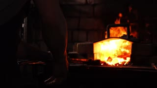 Closeup of a blacksmith's hammer on the background of burning flames of the furnace.