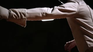 Closeup of a man in helmet for fencing grapple with an opponent on a dark background