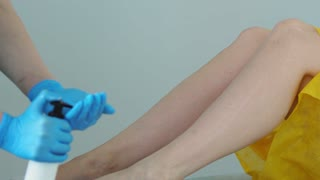 Closeup of the master of hair moisturizing remedy irritation performing foot massage girlfriend after depilation