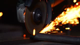 closeup on electric saw and hands of worker with sparks. man working with grinder, close up on tool, sparks fly, real situation picture.