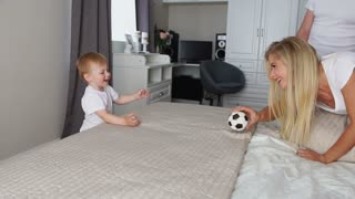 Dad and mom play with the boy on the bed with the ball