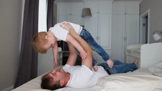 Dad keeps a dignity above himself lying on the bed. A boy in a white T-shirt laughs and smiles from playing with his father