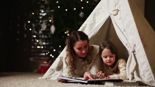 Dressed in white sweaters, mother and daughter read a fairy tale for the night lying with her in the tent of an established house on the background of a Christmas tree