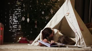 Dressed in white sweaters, mother and daughter read a fairy tale for the night lying with her in the tent of the house