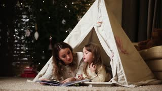Dressed in white sweaters, my mother and daughter read a fairy tale for the night lying with her in the tent of an installed house. girl laughs and mom smiles