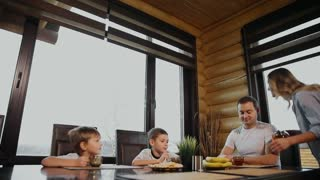 Family of four having Breakfast in his kitchen with large Windows. People are smiling, mother kissing and hugging children. Mother father and two children