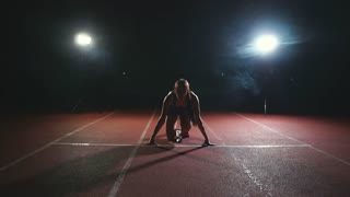 Female athlete on a dark background is preparing to run the cross-country sprint from the pads on the treadmill on a dark background
